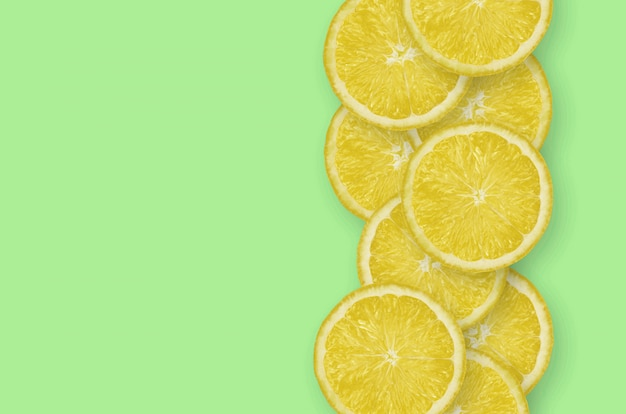 Row of yellow lemon citrus slices on bright lime