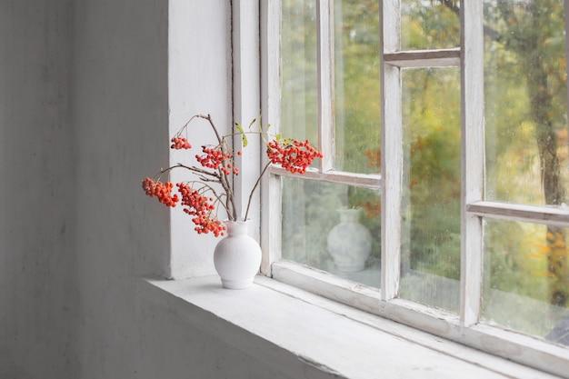 古い白い窓辺に白い花瓶のナナカマドの果実