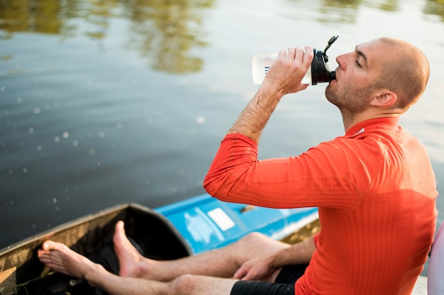 Rowing concept with man drinking water