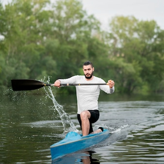 Rowing concept with man holding paddle
