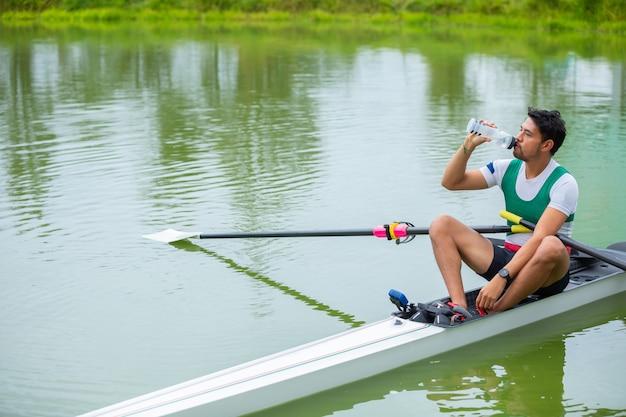 Rowing men on lake drinking water