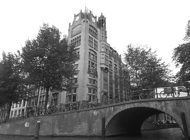 Rows of bicycles parking on a stone bridge of downtown amsterdam, the netherlands in monochrome