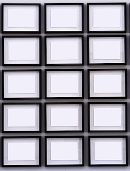 Rows of black picture frames on white walls