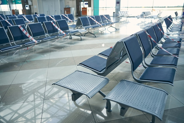 Rows of blue waiting bench at the airport with glass windows