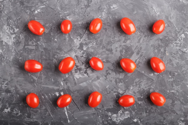 Rows of cherry tomatoes on a black concrete background
