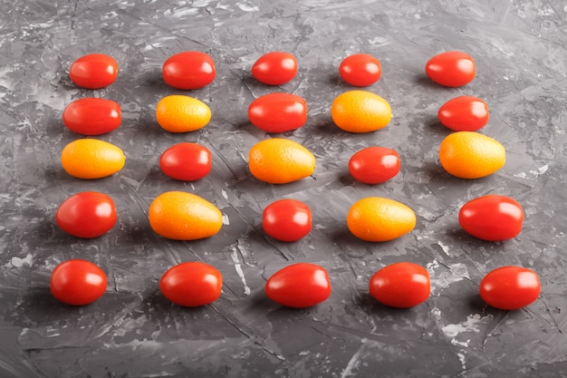 Rows of cherry tomatoes and kumquats, contrast concept.