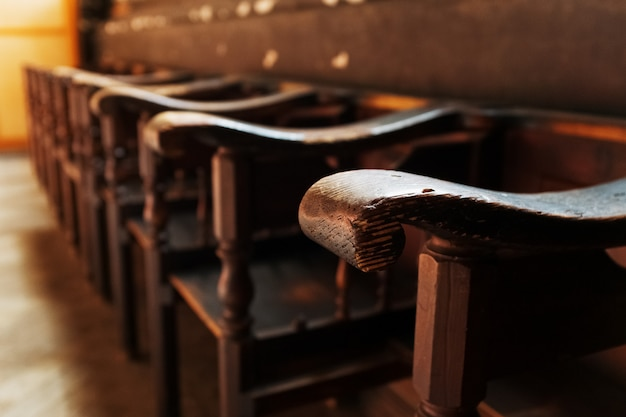 Rows of church benches with sunlight close-up.