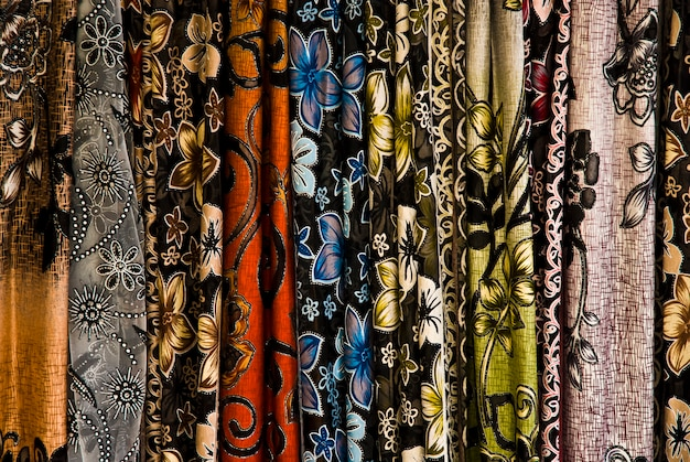 Rows of colorful silk scarves hang on a market stall