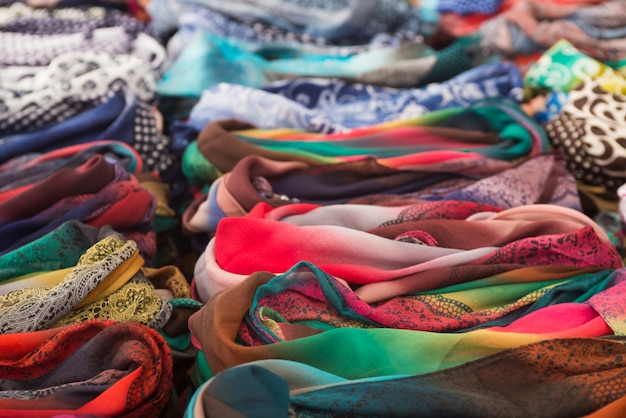 Rows of colorful silk scarves lie on a market stall