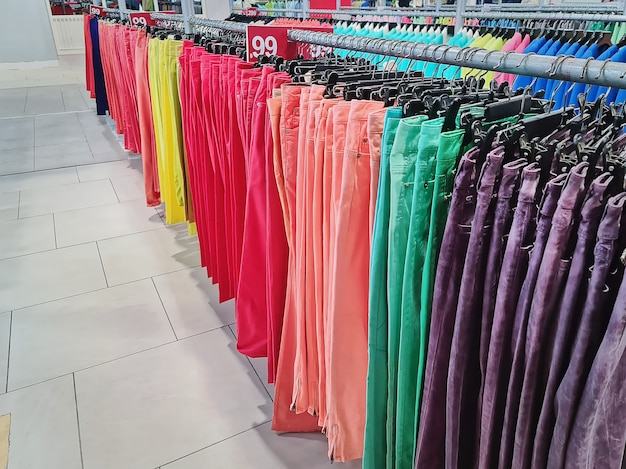 Rows of colorful trousers hanging on the racks at clothing store