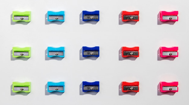 Rows and columns of colourful sharpeners flat lay