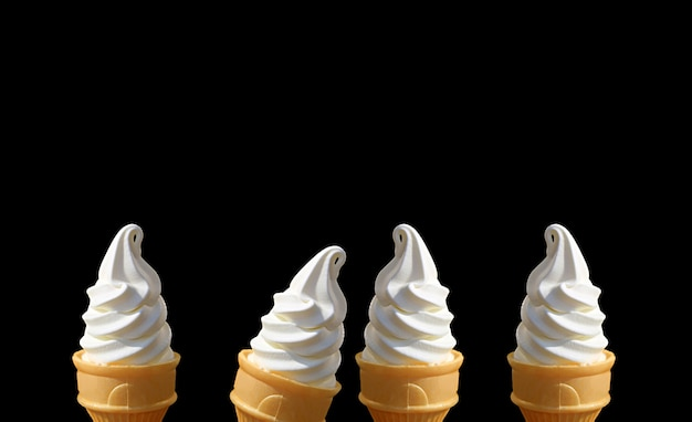 Rows of delectable vanilla soft serve ice cream cones on black background with copy space
