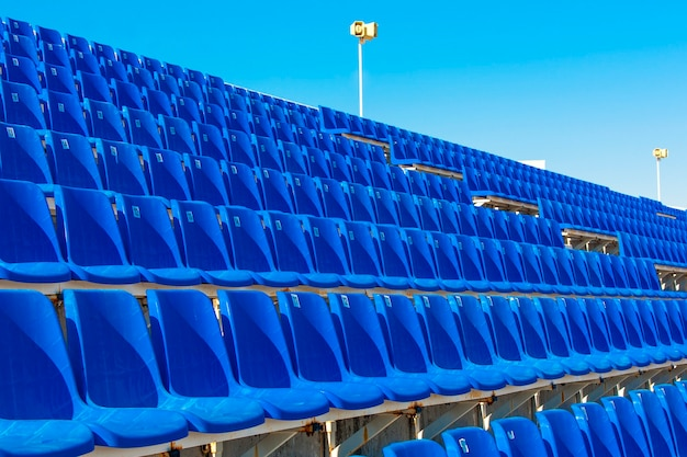 Rows of empty blue color plastic stadium seating on the terrace.