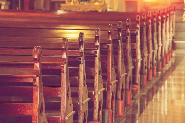 Rows of empty old wooden pews in historic church in thailand
