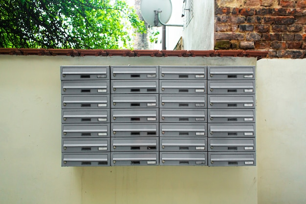 Rows of mailboxes on the street at the entrance to an apartment building.