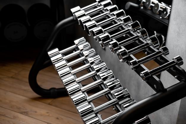 Rows of metal dumbbells on rack for bodybuilding in gym