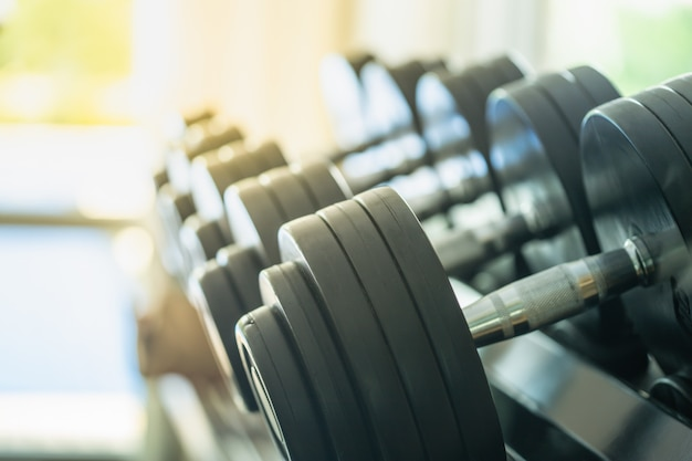 Rows of metal dumbbells on rack in the gym or sport club.