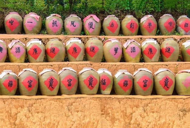 Ряды антикварных китайских банок из глины с рисовым вином и красной бумажной маской на земле