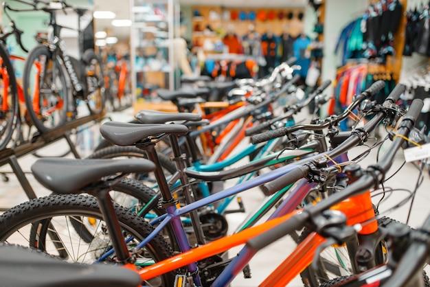 スポーツショップの自転車の列、座席に焦点を当てる