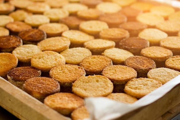 햇빛 아래 비스킷의 행입니다. 노란색과 갈색 쿠키입니다. 고품질 디저트 생산. 오븐에서 만든 shortcrust 반죽.
