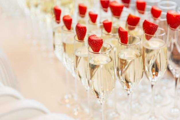 Ряды бокалов шампанского, украшенные клубникой на фуршет. крупный план.