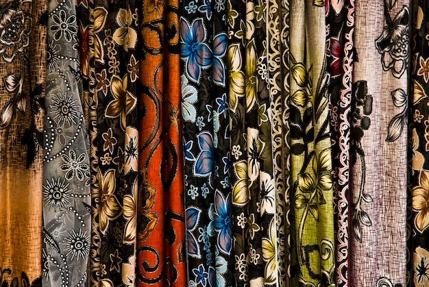 Ряды разноцветных шелковых шарфов висят на прилавке рынка