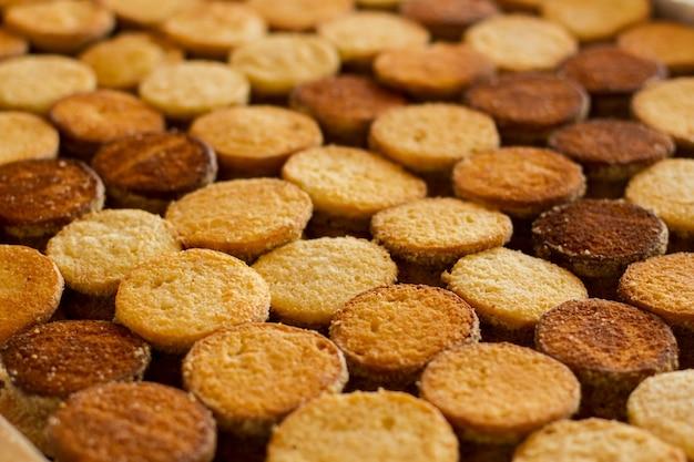 쿠키의 행입니다. 갈색과 노란색 비스킷입니다. 디저트 생산. 최고 품질의 부품만 사용합니다.