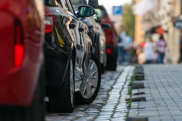 混雑した街の道端に駐車したさまざまな車の列