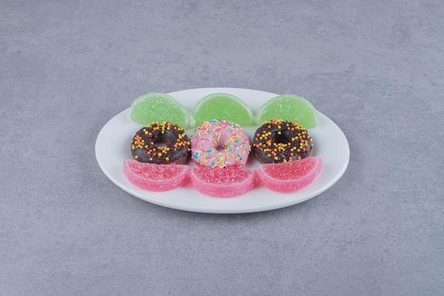Ряды пончиков и мармеладов на блюде на мраморной поверхности