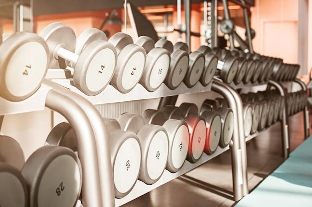 Ряды гантелей в тренажерном зале с большим контрастом и монохромным цветовым тоном
