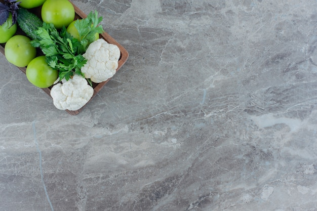 콜리 플라워 조각, 오이, 고수풀 번들 및 아마란스와 함께 그린 토마토의 행은 대리석에 나뭇잎.