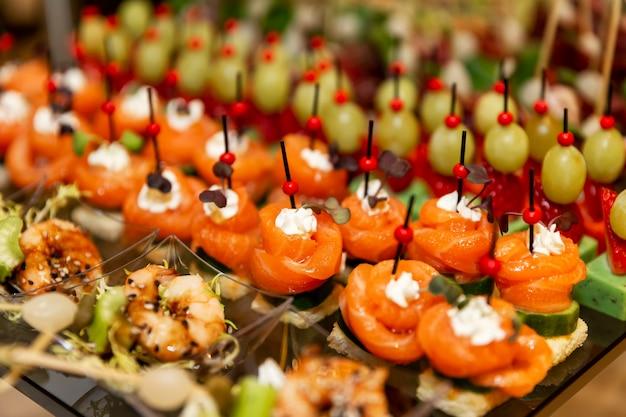 Ряды аппетитных канапе на праздничном столе. питание для деловых встреч, мероприятий и торжеств.