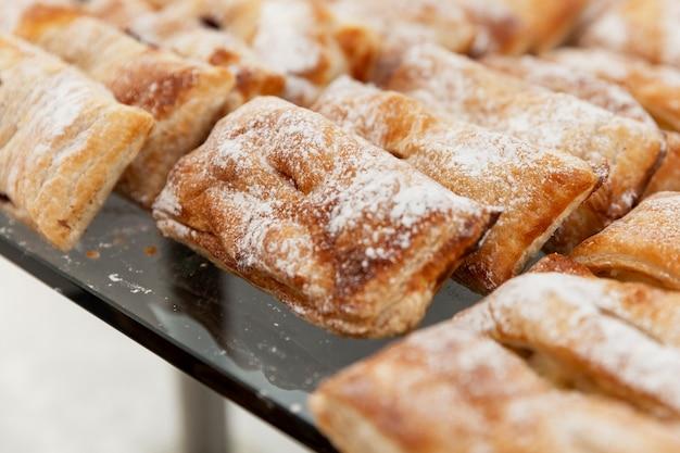 Ряды аппетитной выпечки на подносе на столе. питание для деловых встреч, мероприятий и торжеств.