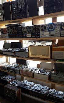 古いアンティークのリールテープレコーダーとラジオテープレコーダーの列が棚に横たわっています