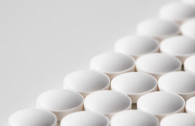 白い背景の上の丸薬の列ヘルスケア医学薬局と病気の概念