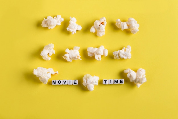 노란색 배경 영화 계획 개념에 팝콘 행과 중간에 영화 시간이라는 단어