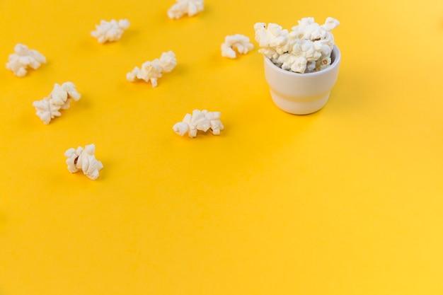 ポップコーンの列とポップコーンと小さなボウル。子供向けの映画館、子供向けの映画