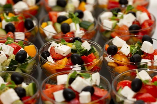 Ряды порционных греческих салатов со свежими овощами. питание для деловых встреч, мероприятий и торжеств.