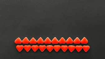 Rows of red heart shape candies on black background