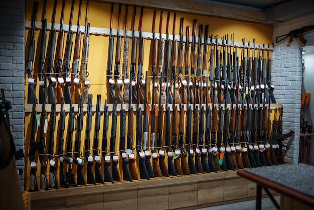 벽에 늘어선 소총, 총기 상점에 진열 된 사람, 아무도. 무기 상점, 사냥 및 스포츠 촬영 취미에있는 사냥꾼을위한 euqipment
