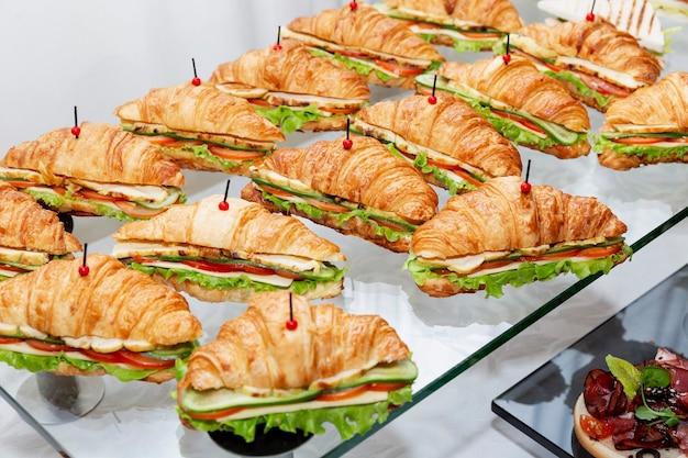 テーブルの上のサンドイッチクロワッサンの列。ビジネスミーティング、イベント、お祝いのケータリング。
