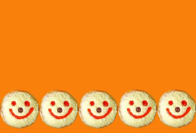 コピースペースと鮮やかなオレンジ色の背景に笑顔のココナッツフレークジェリードーナツの列