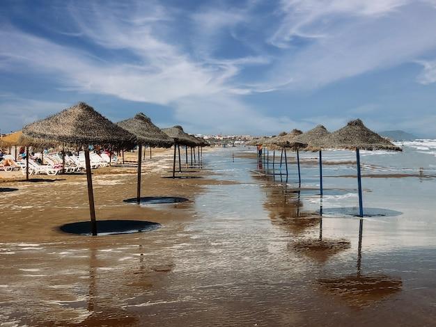 여름에 푸른 하늘의 배경에 모래 해변을 따라 배치 짚 우산의 행