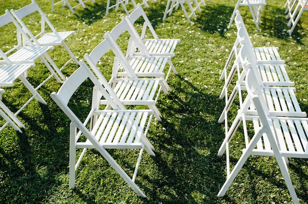 芝生の上の白い折りたたみ椅子の行