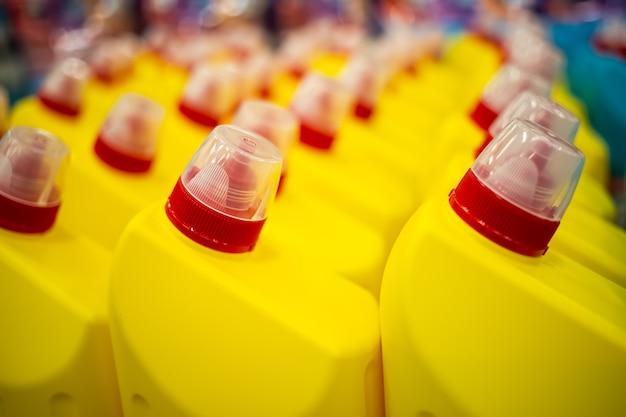 Ряды желтых пластиковых бутылок с красной крышкой с бытовой химией крупным планом мягкий фокус b