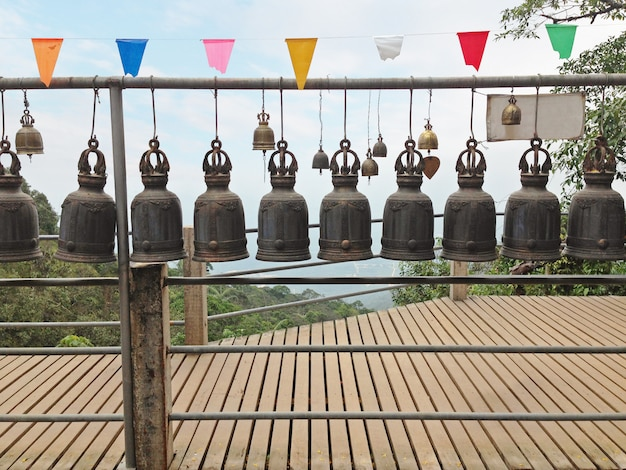 The rows of stenciled thai temple bells hanged along the wooden pathway with nature and sky background