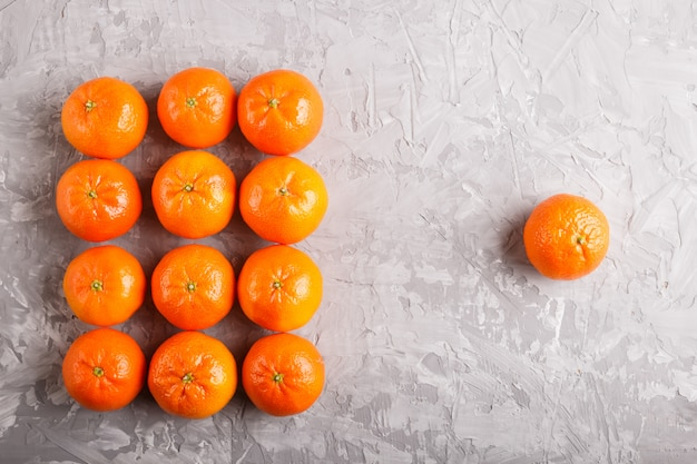 Rows of tangerines forming a rectangle and one tangerine on gray