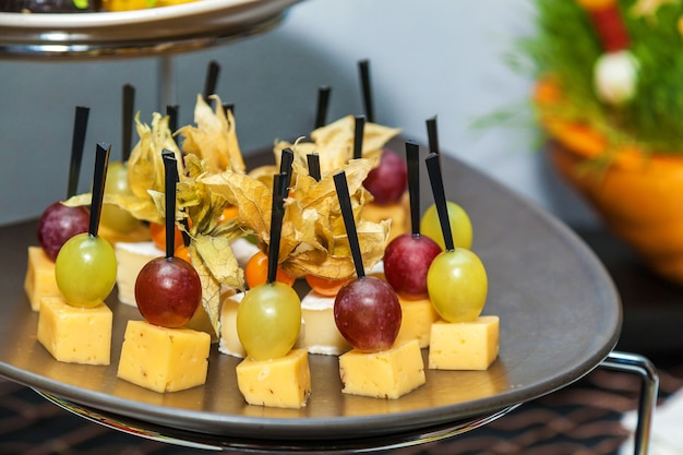Rows of tasty mini canapes with brie cheese and grapes.canape with cheese and grape