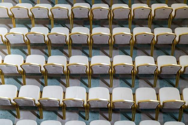 Rows of traditional hard wood chairs with soft cushion and golden edging for formal meetings