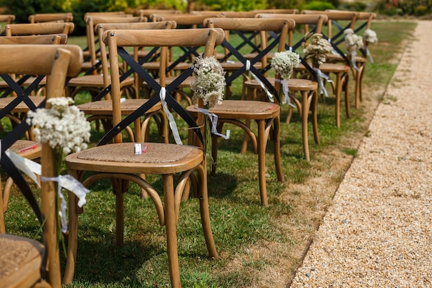 Rows of wooden chairs for guests. wedding ceremony decorated with flowers  in rustic style